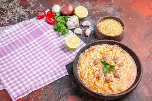 Vista laterale della deliziosa zuppa di pollo con noodles verdi e cucchiaio su rosa asciugamano spogliato bottiglia di olio aglio pomodori limone e taccuino su sfondo scuro