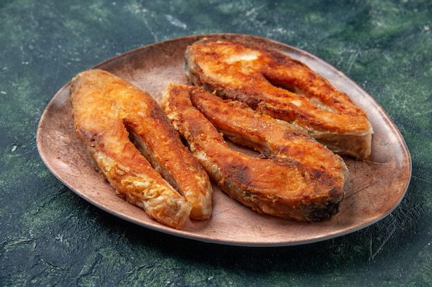Side view of delicious fried fish on a brown plate on the left side on mix colors table with free space