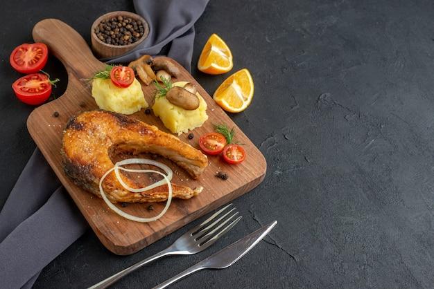 Vista laterale del delizioso pasto di pesce fritto con funghi verdure formaggio su tavola di legno fette di limone pepe su posate asciugamano di colore scuro impostato su superficie nera in difficoltà