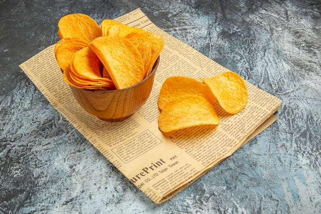 Side view of delicious homemade chips on newspaper on gray table