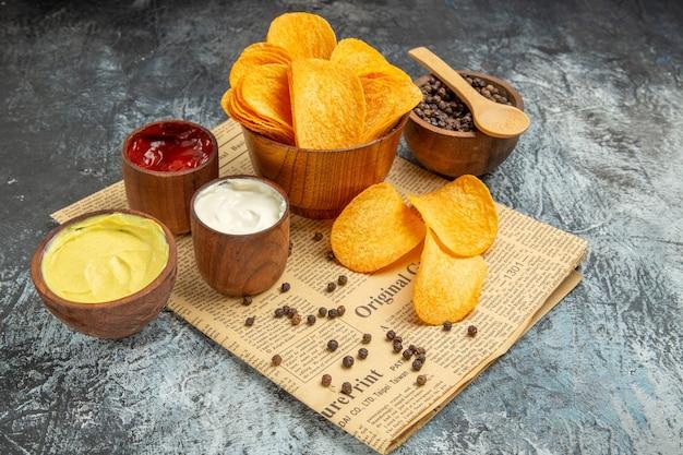 Vista laterale di deliziose patatine fatte in casa e pepe ciotola maionese ketchup e salsa con cucchiaio sul giornale sul tavolo grigio