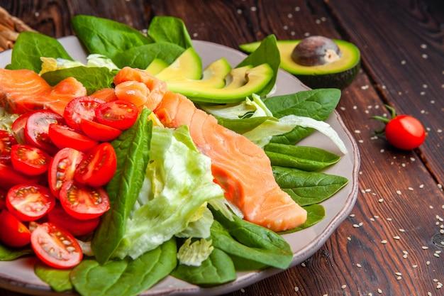 Вид сбоку вкусная еда в тарелку с авокадо на деревянных фоне.