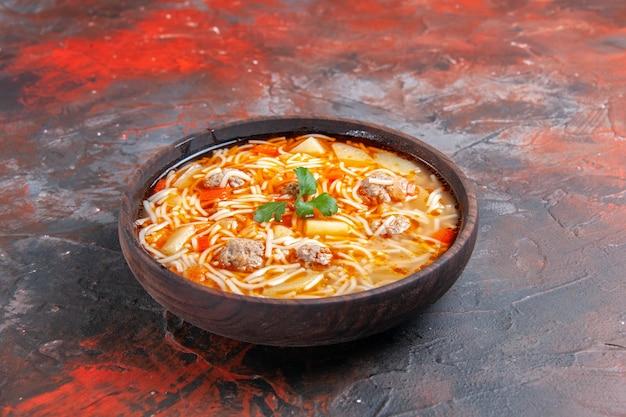 Vista laterale di una deliziosa zuppa di noodle con pollo in una ciotola marrone sullo sfondo scuro