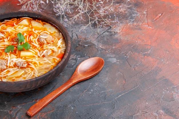 Vista laterale della deliziosa zuppa di noodle con pollo in una ciotola marrone e cucchiaio sullo sfondo scuro
