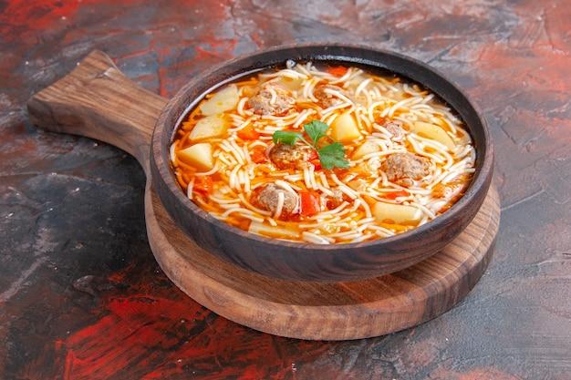 Vista laterale di deliziosa zuppa di noodle con pollo su tagliere di legno su sfondo scuro
