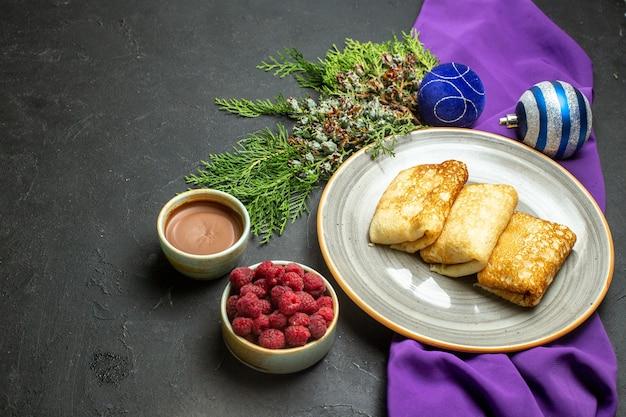 Vista laterale di deliziosi accessori per la decorazione di pancake su asciugamano viola e lampone al cioccolato su sfondo nero