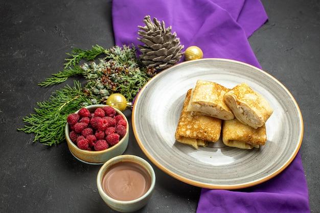 Vista laterale di deliziose frittelle su un piatto bianco di cioccolato e accessori per la decorazione di lamponi su un asciugamano viola su sfondo nero