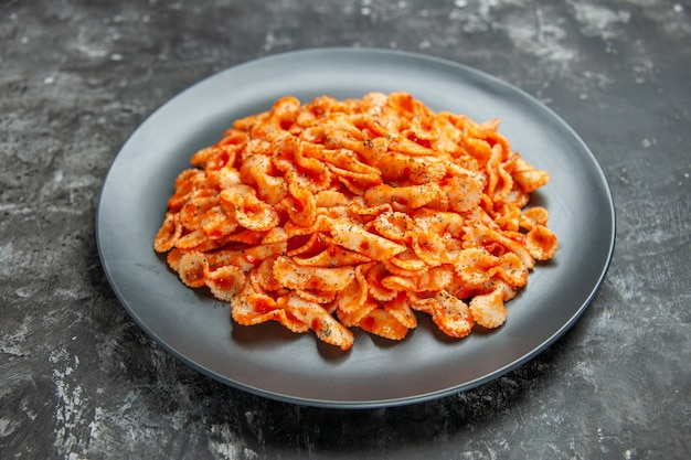 Side view of delicious pasta meal on a black plate for dinner on dark background