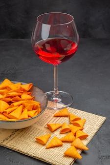 Vista laterale di deliziose patatine dentro e fuori la ciotola e vino rosso in un bicchiere su un vecchio giornale su sfondo nero