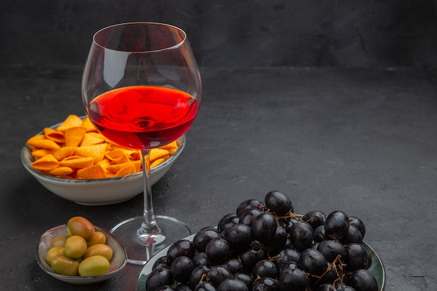 Side view of delicious red wine in a glass goblet and various snacks on a black background