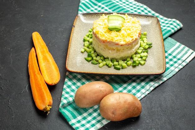 Vista laterale di una deliziosa insalata servita con cetriolo tritato su carote e patate spogliate di asciugamano verde piegato a metà su sfondo scuro
