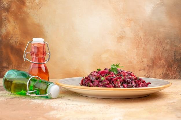 Vista laterale di una deliziosa insalata con barbabietola e fagioli e caduta di due bottiglie di olio su sfondo a colori misti
