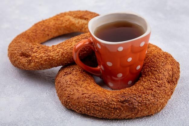 Vista laterale di deliziosi bagel turchi di sesamo con una tazza di tè su uno sfondo bianco
