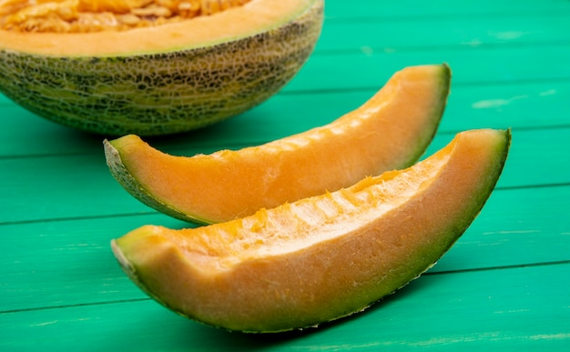 Side view of delicious and sliced cantaloupe melon on green wooden surface