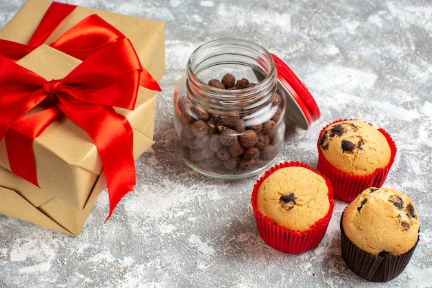 Side view of delicious small cupcakes and chocolate in a glass pot next to gift with red ribbon on ice surface
