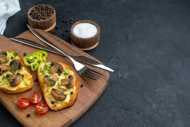 Side view of delicious snacks with mushroom fresh vegetables and cutlery set on wooden cutting board white towel spices on black background