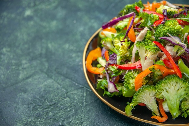 Side view of delicious vegan salad in a plate with various fresh vegetables on dark background