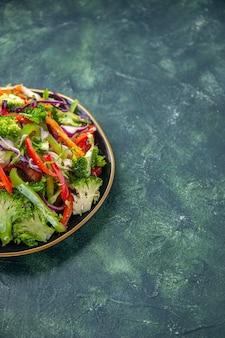 Vista laterale di una deliziosa insalata vegana in un piatto con varie verdure fresche sul lato destro su sfondo scuro