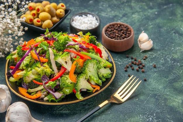 Vista laterale di deliziosa insalata vegana in un piatto con varie verdure e forchetta pepe verde olive nere aglio su sfondo scuro