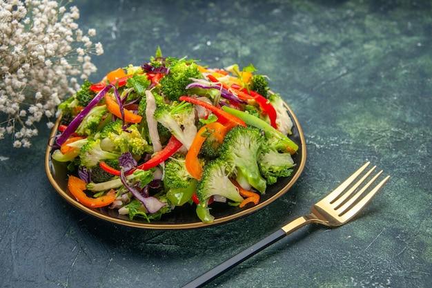 Vista laterale di deliziosa insalata vegana in un piatto con varie verdure e fiore bianco forchetta su sfondo scuro