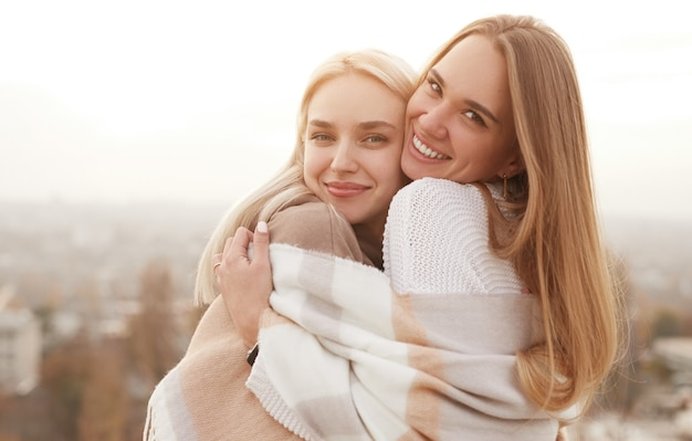 Side view of delighted female best friends cuddling