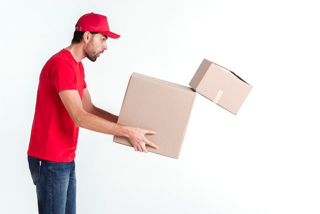 Side view delivery boy holding parcel post boxes and drops one