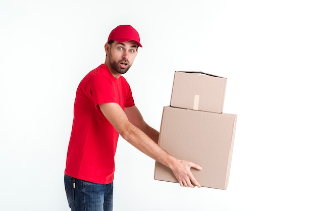 Side view delivery boy holding parcel post boxes