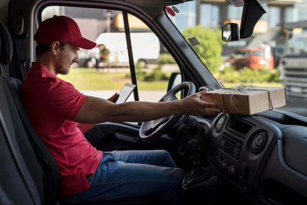 Uomo di consegna vista laterale in auto