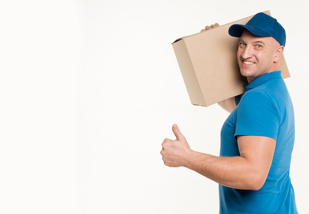Side view of delivery man carrying cardboard box and giving thumbs up