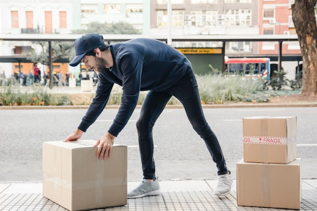 Side view of a delivery man carrying cardboard box