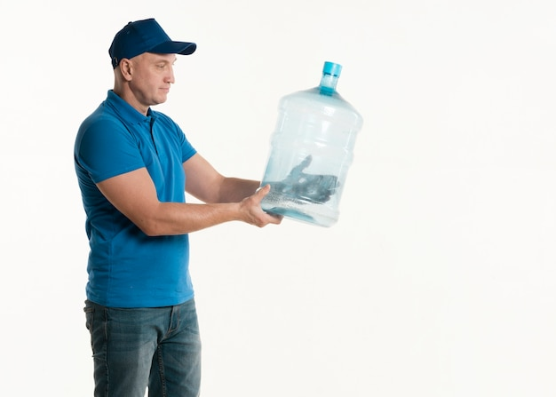 Side view of delivery man holding water bottle