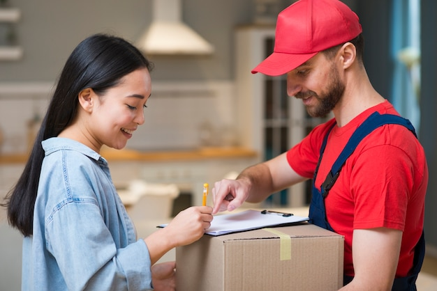 Side view of delivery man showing woman where to sign to receive order