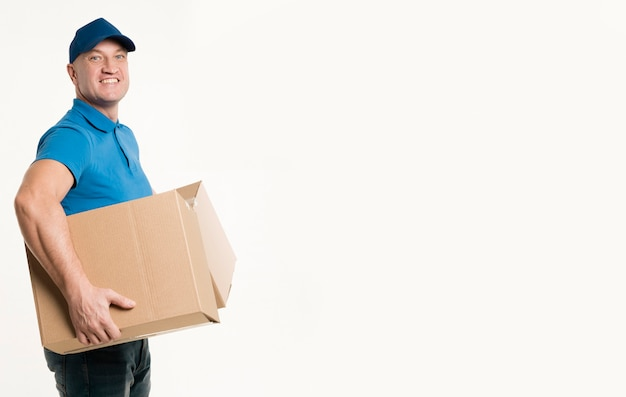 Side view of delivery man smiling while holding cardboard boxes