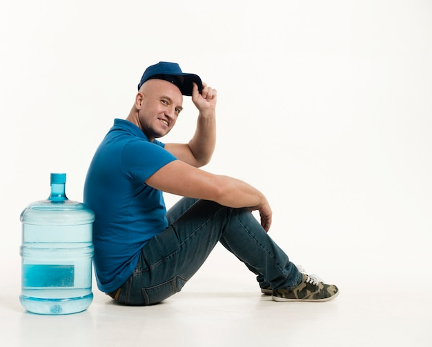 Side view of delivery man wearing cap posing with water bottle