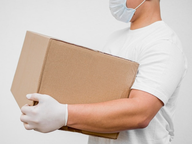 Side view delivery man wearing mask