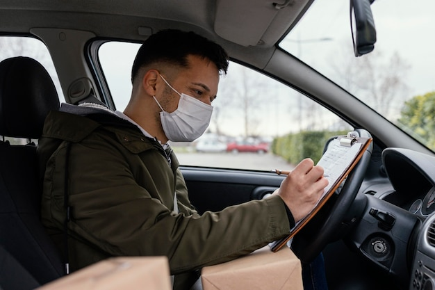 Side view delivery man with mask in car