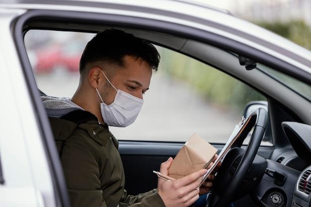 Uomo di consegna vista laterale con maschera in auto