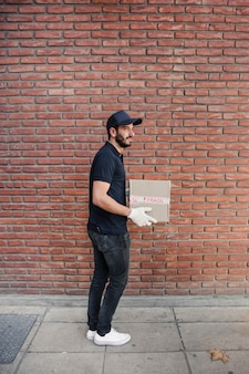 Side view of a delivery man with parcel in front of brickwall