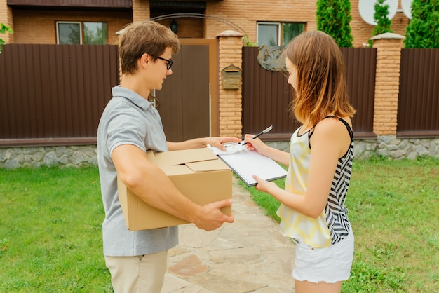 Side view of delivery man and young woman putting a signature of delivery package, standing near the delivery worker holding a cardboard box. delivery concept. outdoors.