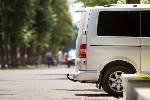 녹색 나무 보케 복사 공간 배경에 보행자의 흐릿한 실루엣과 함께 여름 도시 거리 포장에 주차 된 흰색 승객 중형 고급 미니 버스 밴의 측면 보기 세부 사항.