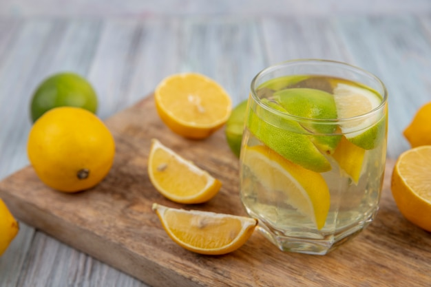 まな板の上にライムのくさびと半分のオレンジとレモンが入ったグラスに水をデトックスする側面図