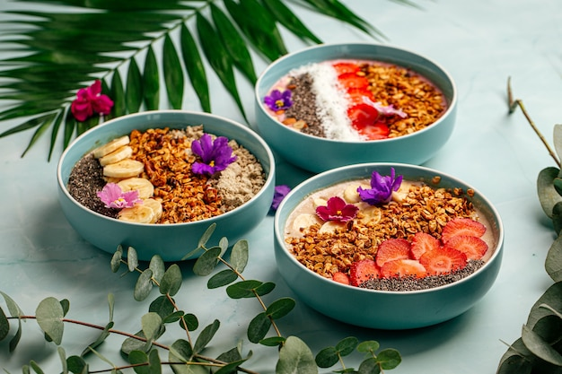 Side view on dfferent smoothie bowls with fruits and granola