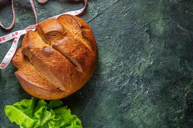 Vista laterale del pane nero dietetico e del fascio di metri verdi sul lato destro su sfondo di colori scuri