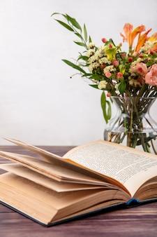 Vista laterale di diversi fiori luminosi e meravigliosi con foglie su un vaso di vetro sulla superficie bianca