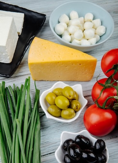 Side view of different kinds of cheese with green onion, pickled olives and fresh tomatoes on grey wooden table