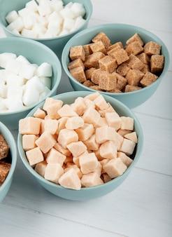 Vista laterale di diversi tipi di zucchero grumo in ciotole su sfondo bianco