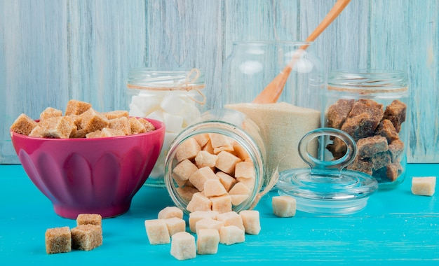 Vista laterale di diversi tipi di zucchero in ciotole e barattoli di vetro su fondo di legno blu