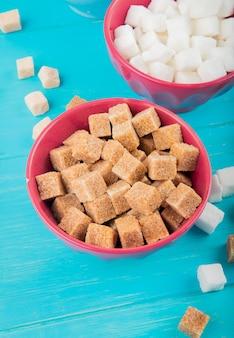 Vista laterale di diversi tipi di zollette di zucchero in ciotole su fondo di legno blu