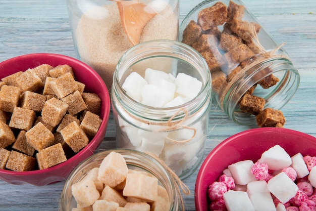 Side view of different types of sugar in glass jars on rustic background