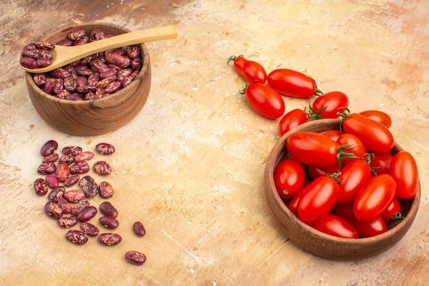 Vista laterale dello sfondo della cena con fagioli all'interno e all'esterno della pentola marrone con cucchiaio e pomodori su sfondo di colore misto